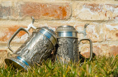 Zwei Bierkrüge auf dem Gras nahe der Backsteinmauer Lizenzfreie Stockfotos