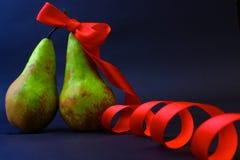 Zwei Birnen eine in einem roten Geschenkband Stockbild