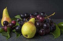 Zwei Birnen und Gruppe von blauen Trauben auf Küche übersteigen Lizenzfreies Stockfoto