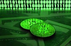 Zwei bitcoins Lügen auf einem Stapel von Dollarscheinen auf dem Hintergrund eines Monitors, der ein binär Code von hellgrünen nul Lizenzfreie Stockfotos
