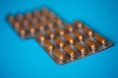 Zwei Blasen mit braunen Pillenkapseln auf einem blauen Hintergrund heal stockbild