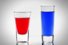 Zwei blau und rotes Cocktail in den vollen transparenten Schnapsgläsern mit Stockbilder