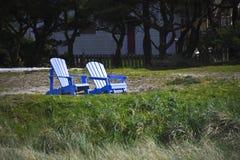 Zwei blaue Adirondack-Stühle auf einem Strand Stockbild