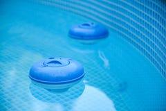 Zwei blaue Chlor-Zufuhren, die im Pool sitzen stockfotografie