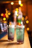 Zwei blaue Cocktails mit Zitrone auf der Bar, unscharfer Hintergrund Stockfotos