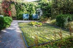 Zwei blaue Designgartenstühle für den Teich, dem mit bedeckt wird Lizenzfreies Stockfoto
