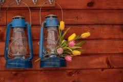 Zwei blaue Kerosinlampen mit Blumenstrauß von Tulpen auf einem hölzernen Hintergrund Lizenzfreie Stockfotografie