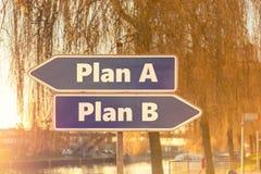 Zwei blaue Pfeile in der entgegengesetzten Richtung mit dem Aufschrift Plan A und Plan B mit sonnigem Hintergrund einer Stadt stockbilder