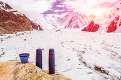 Zwei blaue Reise Thermoses Thermo Flaschen und Schale auf Stein- und niedrigem Lager im Hochgebirge lizenzfreie stockfotografie