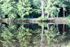 Zwei blaue Stühle durch den Fluss Stockfoto