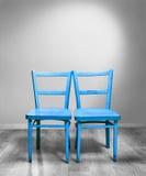 Zwei blaue Stühle im grauen Raum Stockbild
