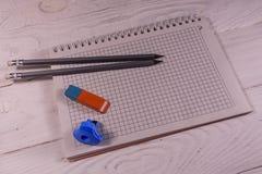 Zwei Bleistifte, Bleistiftspitzerradiergummi und Notizblock auf Holztisch Stockfotos