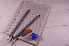 Zwei Bleistifte, Bleistiftspitzerradiergummi und Notizblock auf Holztisch Lizenzfreie Stockfotos