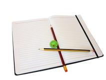 Zwei Bleistifte und ein Radiergummi auf einem Notizbuch Lizenzfreies Stockfoto