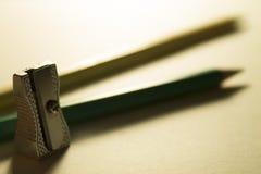 Zwei Bleistifte von verschiedenen Farben und ein Bleistiftspitzer in der Hintergrundbeleuchtung Lizenzfreie Stockbilder