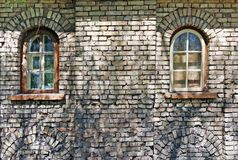 Zwei blinde Fenster im Gelb ruinierten Backsteinmauer des hohen Alters Lizenzfreie Stockfotografie