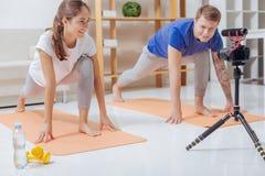 Zwei Bloggers, die Yoga vor ihrer Videokamera üben Lizenzfreies Stockfoto