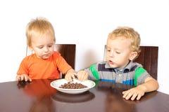 Zwei blonde Brüder essen Rennnüsse Stockfotos
