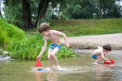 Zwei blonde Brüder haben Spaß auf dem Strand in einem sonnigen Sommertag Lizenzfreies Stockbild