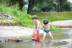Zwei blonde Brüder haben Spaß auf dem Strand in einem sonnigen Sommertag Stockfotos