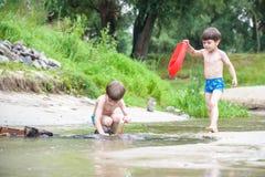 Zwei blonde Brüder haben Spaß auf dem Strand in einem sonnigen Sommertag Lizenzfreies Stockfoto
