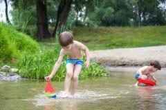 Zwei blonde Brüder haben Spaß auf dem Strand in einem sonnigen Sommertag Stockbild