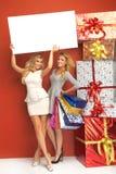 Zwei blonde Frauen mit viel von Geschenken Stockfotografie