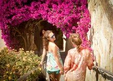 Zwei blonde Freunde, die die Treppe hinunter die Blumen durchlaufen Stockfotografie