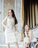 Zwei blonde gelockte Frisuren der hübschen Zwillingsschwestern im Luxushausinnenraum zusammen, reiches Konzept der jungen Leute Lizenzfreie Stockbilder