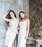 Zwei blonde gelockte Frisuren der hübschen Zwillingsschwestern im Luxushausinnenraum zusammen, reiches Konzept der jungen Leute Lizenzfreie Stockfotos