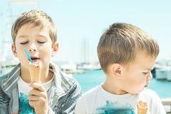 Zwei blonde Kinder, die Eiscreme essen Kinder mit einem Ausdruck des Glückes Eiscreme essend Lizenzfreies Stockfoto