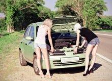 Zwei blonde Mädchen, die das defekte Auto bereitstehen Lizenzfreie Stockfotografie