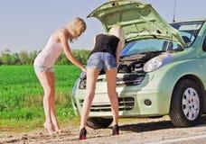 Zwei blonde Mädchen, die das unterbrochene Auto bereitstehen Stockfotos