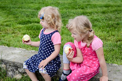 Zwei blonde Mädchen, die einen Apfel essen Lizenzfreie Stockfotos
