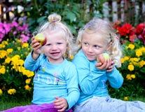 Zwei blonde Mädchen, die einen Apfel halten Stockfoto