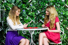 Zwei blonde Mädchen, die Spaß in einem Café plaudern und haben Lizenzfreie Stockfotos