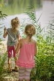 Zwei blonde Mädchen durch den Fluss Stockfotografie
