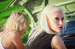 Zwei blonde Mädchen stehen das defekte Auto bereit Stockbilder