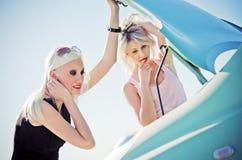 Zwei blonde Mädchen stehen das unterbrochene Auto bereit Lizenzfreie Stockbilder