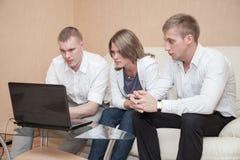 Zwei blonde Männer und eine Frau, die zusammen am Glastisch sitzen und Laptop verwenden Lizenzfreie Stockfotos