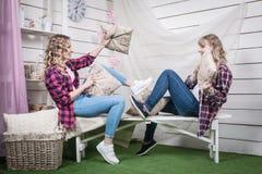 Zwei blonde Schwestern im Raum mit weißen Wänden Stockbild