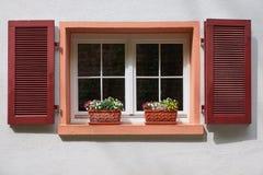 Zwei Blumentöpfe auf dem alten Fenster mit hölzernen Fensterläden auf Weiß Stockfotografie