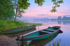 Zwei Boote auf dem Fluss. Nebelige Landschaft. Stockbild