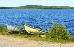 Zwei Boote auf dem Ufer des blauen Sees Stockfotos