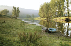 Zwei Boote auf dem Ufer von kleinem Fluss im Sommer Stockfotografie