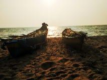 Zwei Boote auf Seeufer von Arabischem Meer während des Sonnenuntergangs an Kerala-Küste lizenzfreie stockfotografie