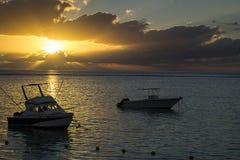 Zwei Boote im Meer bei Sonnenuntergang Stockfotos