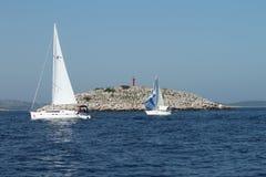 Zwei Boote vor einem roten Leuchtturm - Nationalpark Kornati lizenzfreie stockfotos