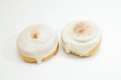 Zwei Brötchen mit der Zuckerglasur und Zimt lokalisiert auf Weiß Stockfotos