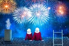 Zwei Brüder auf der Heiligen Nacht, die auf dem Dach des Hauses und des Blickes an aufpassenden Feuerwerken sitzt stockfotografie